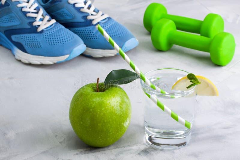 Composizione in sport con la mela di vetro dell'acqua dell'articolo sportivo fotografie stock libere da diritti
