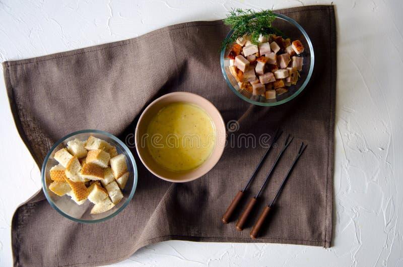 Composizione su una base piana con un vaso della fonduta di formaggio deliziosa su una tavola concreta fotografia stock libera da diritti