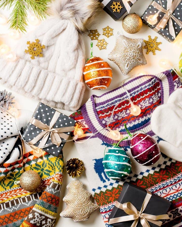 Composizione in umore di Natale con il Natale maglione, cappello, presente e luci Disposizione piana di concetto di inverno, vist immagine stock