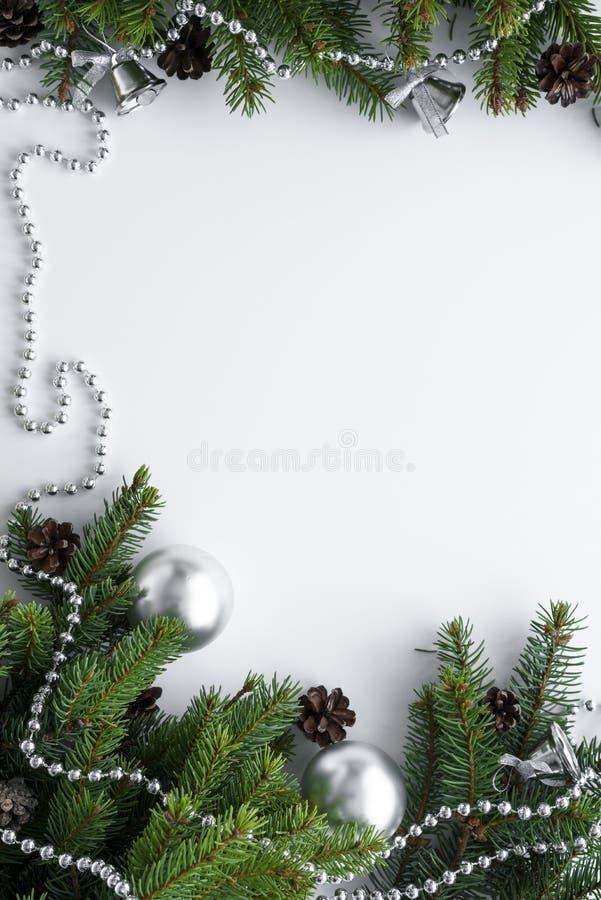 Composizione verticale in natale con la decorazione festiva d'argento quali le bagattelle, la catena e le campane Elementi della  fotografia stock libera da diritti