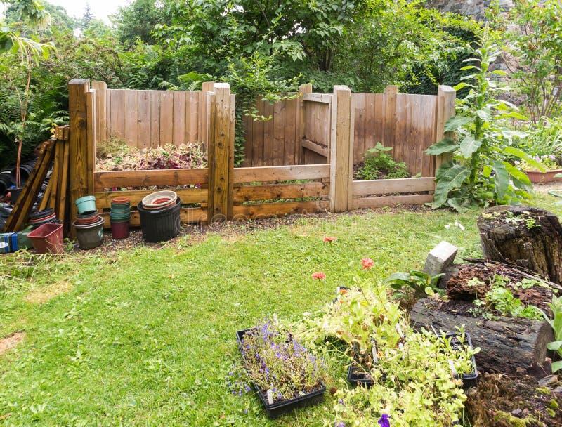 Compost bins. Wooden compost bins in garden setting stock photos