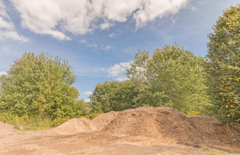 Compost pile of vegetation matter and green trees. Brown compost pile of vegetation matter and green trees , blue sky and white clouds, Berkshires, Pittsfield royalty free stock photography