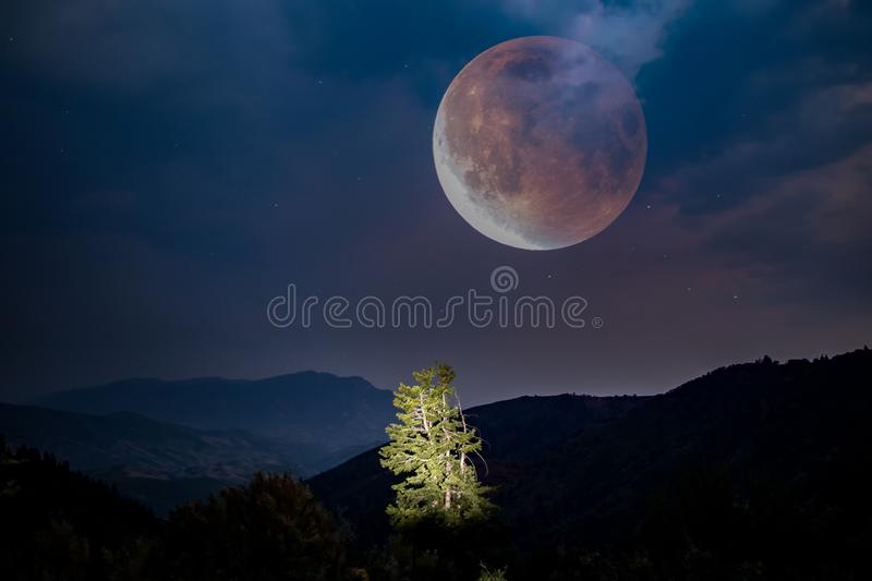 Composted dreamy picture of a giant moon over the mountains stock photo