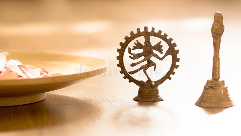 Compostion de sculpture en shiva de danse avec la cloche et une cuvette de pétales images libres de droits
