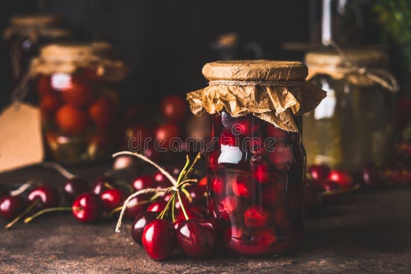 Compota de fruto da cereja nos frascos de vidro na mesa de cozinha rústica escura Fim acima Alimento biológico preservado do jard fotografia de stock