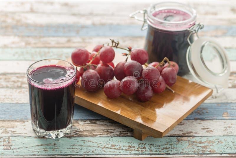 Compota e uvas frescas do suco de uva na tabela do vintage fotografia de stock