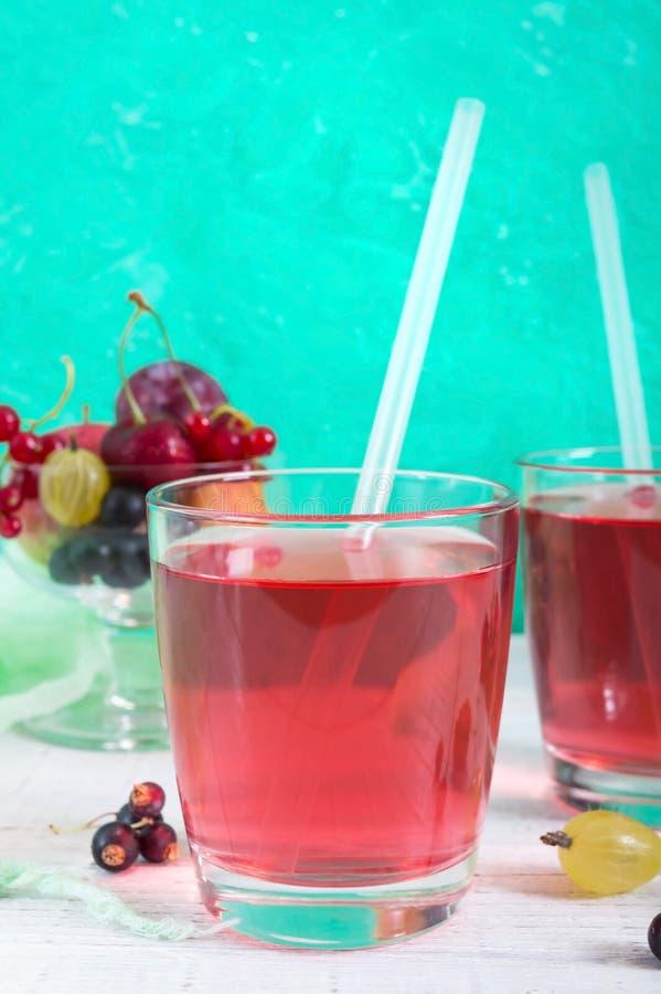 Compote μούρων Ποτό βιταμινών φρούτων στο γυαλί και ώριμα φρέσκα μούρα σε ένα φωτεινό υπόβαθρο στοκ εικόνα