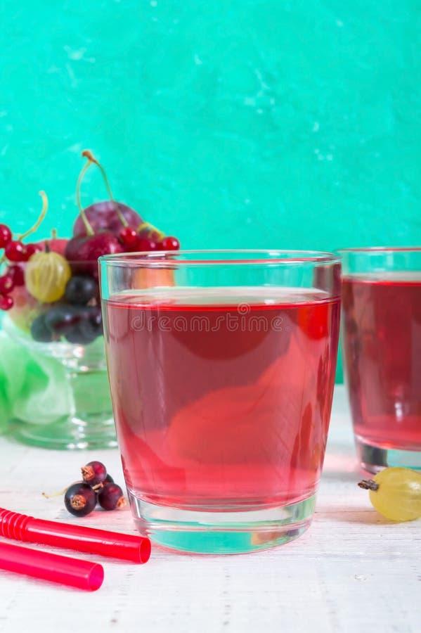 Compote μούρων Ποτό βιταμινών φρούτων στο γυαλί και ώριμα φρέσκα μούρα σε ένα φωτεινό υπόβαθρο στοκ εικόνες με δικαίωμα ελεύθερης χρήσης