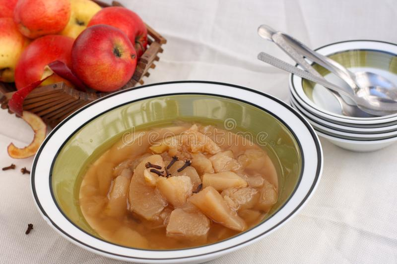 Compote. Fresh homemade apple compote with cinnamon in a ceramic bowl, dried cloves, apple and matching set of bowls with spoons in the back stock photos