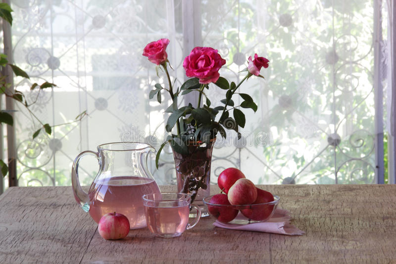 Compote from apples in a transparent jug and a bouquet of roses stock photography