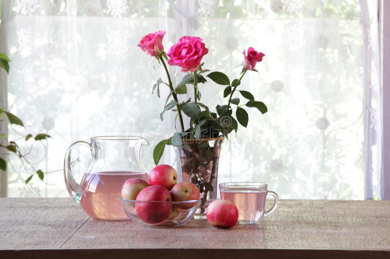 Compote from apples in a transparent jug on a wooden table royalty free stock photo