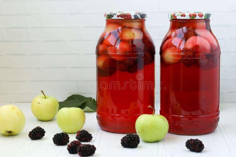 Compote of berries and apples in jars on a table on a white background. royalty free stock photo