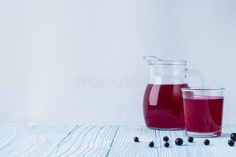 Compote fraîche de cassis dans le décanteur en verre avec le plein verre photo stock