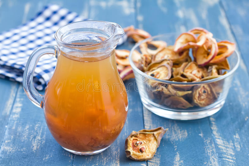 Compote. In a jug and dry fruits on a wooden table royalty free stock image