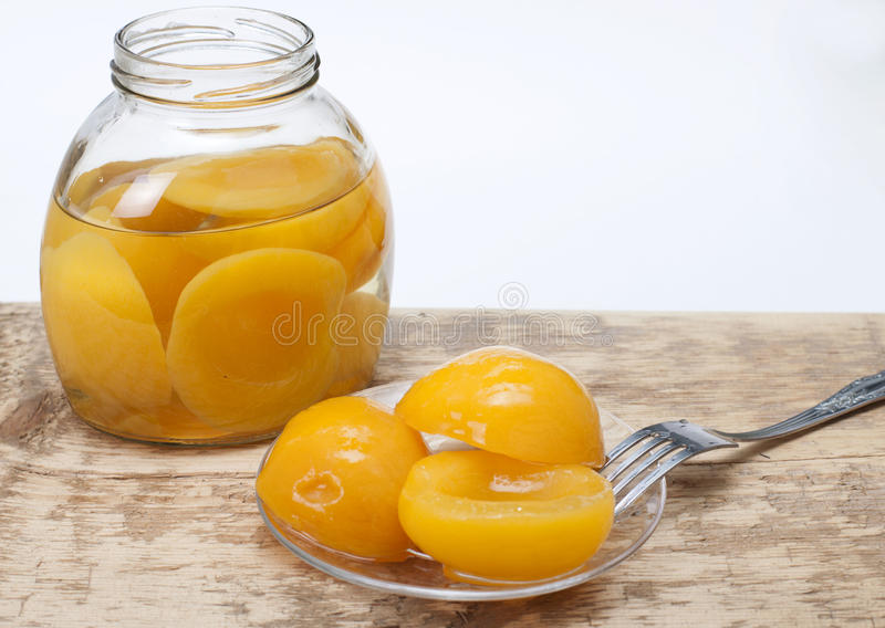 Compote of peaches. In a glass jar, and in the plate on wooden table with a white background royalty free stock photos
