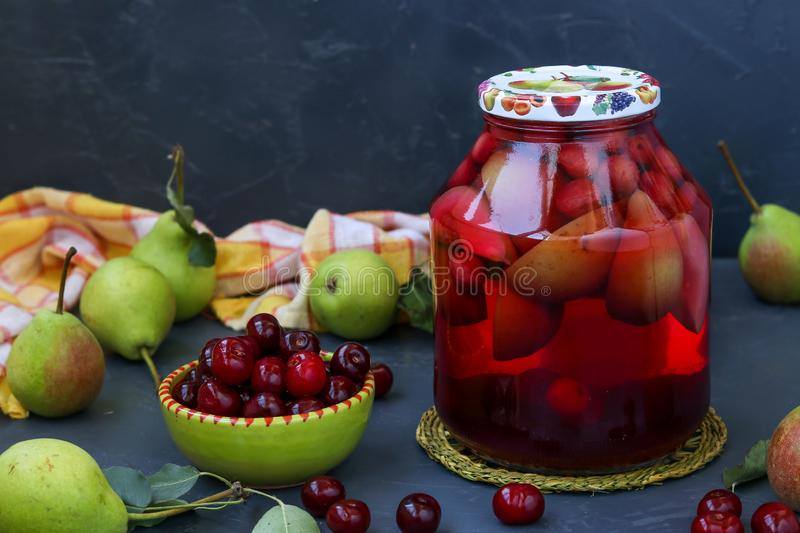 Compote of pears and cherries in jar on dark background, harvest for the winter, horizontal orientation, close-up. Compote of pears and cherries in jar on dark royalty free stock images