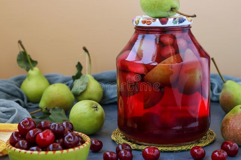 Compote of pears and cherries in jar on table, harvest for the winter, horizontal photo royalty free stock photos