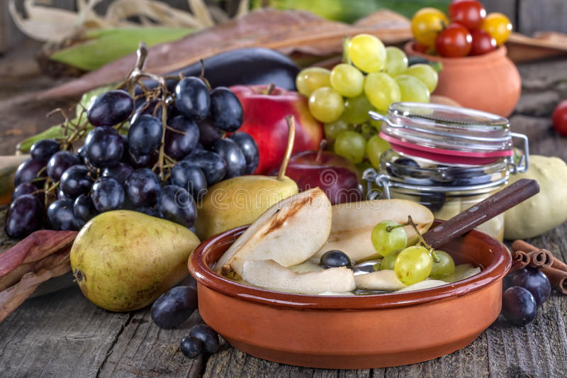 Compote of pears with grapes. Fruit compote of pears with grapes surrounded by fresh fruit and vegetables royalty free stock images