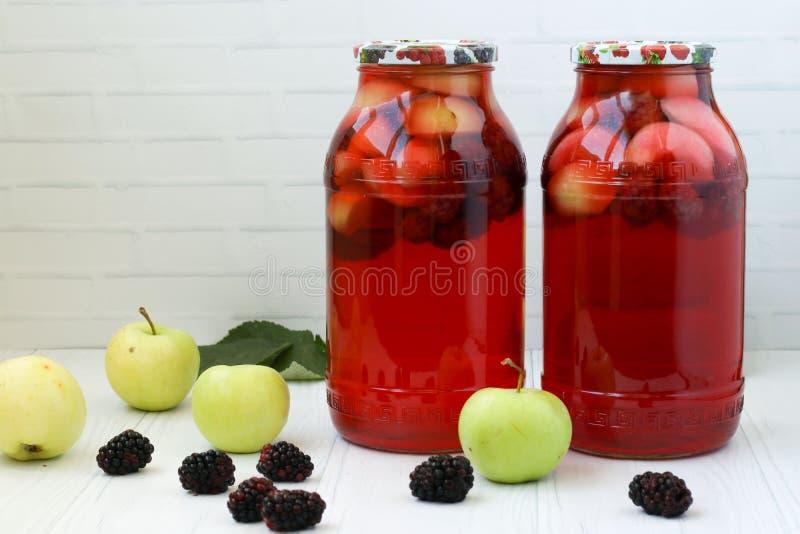 Compote van bessen en appelen in kruiken op een lijst aangaande een witte achtergrond royalty-vrije stock foto