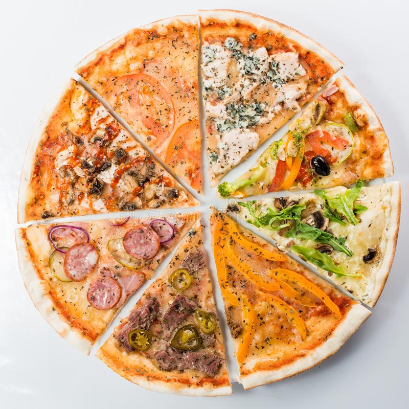 Compound pizza from slices of different pizzas on a light background stock photos