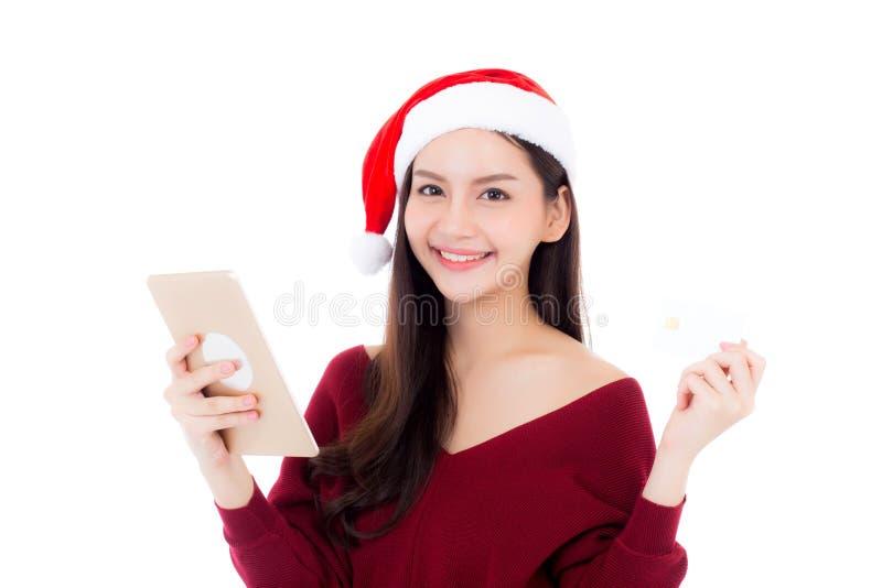 Compra asiática bonita da jovem mulher com cartão de crédito e tabuleta no feriado do Natal, menina guardar com pagamento isolada imagens de stock royalty free