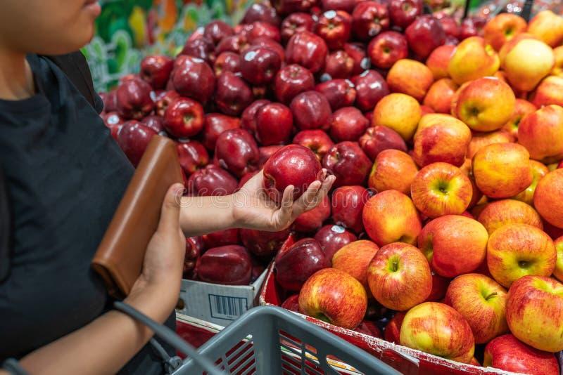Compra asiática da mulher e escolha da maçã vermelha no supermercado foto de stock royalty free
