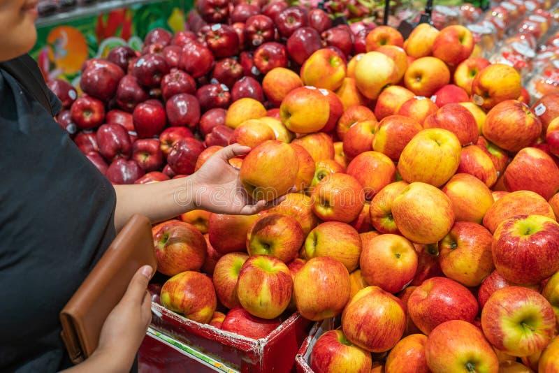Compra asiática da mulher e escolha da maçã vermelha no suporte de fruto imagens de stock royalty free