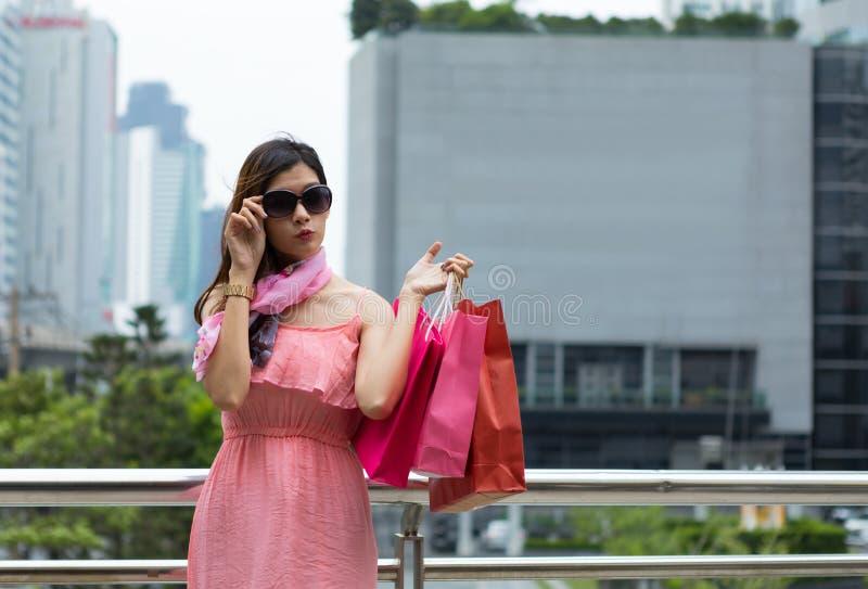 Compra bonita da mulher em óculos de sol vestindo do vestido do sibilo com s fotos de stock royalty free