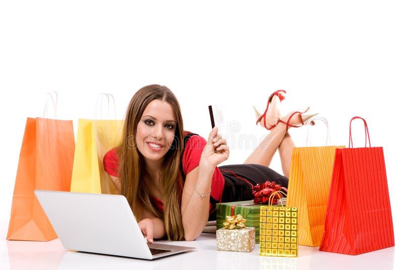 Compra bonita da mulher nova sobre o Internet imagem de stock
