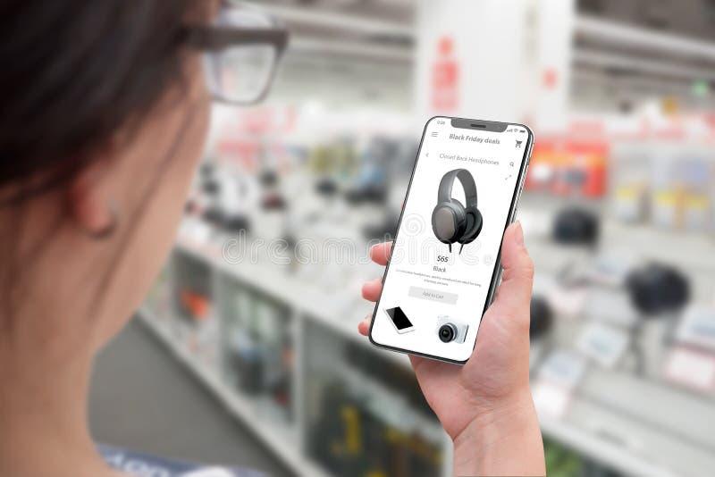 Compra com smartphone Mulher que usa a site em linha e a busca da loja para discontos da tecnologia para sexta-feira preta foto de stock