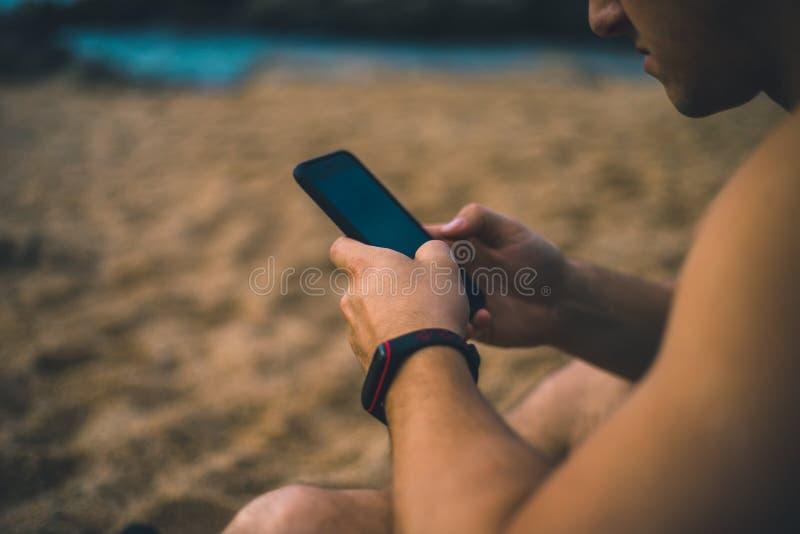 Compra con un teléfono elegante en la playa imagenes de archivo
