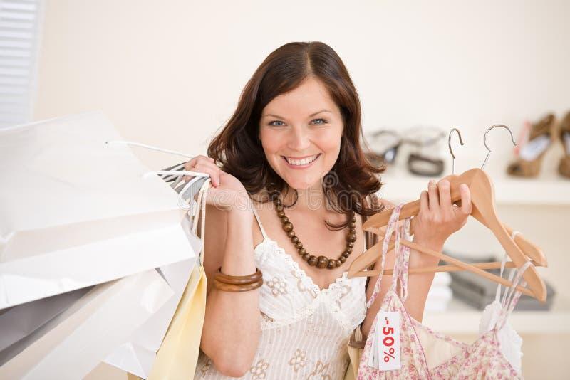 Compra da forma - a mulher feliz escolhe a roupa da venda fotografia de stock royalty free