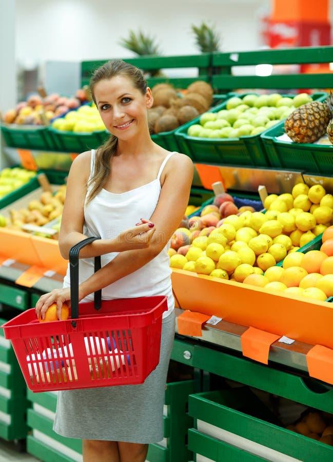 Compra da jovem mulher em um supermercado no departamento do fruto fotografia de stock
