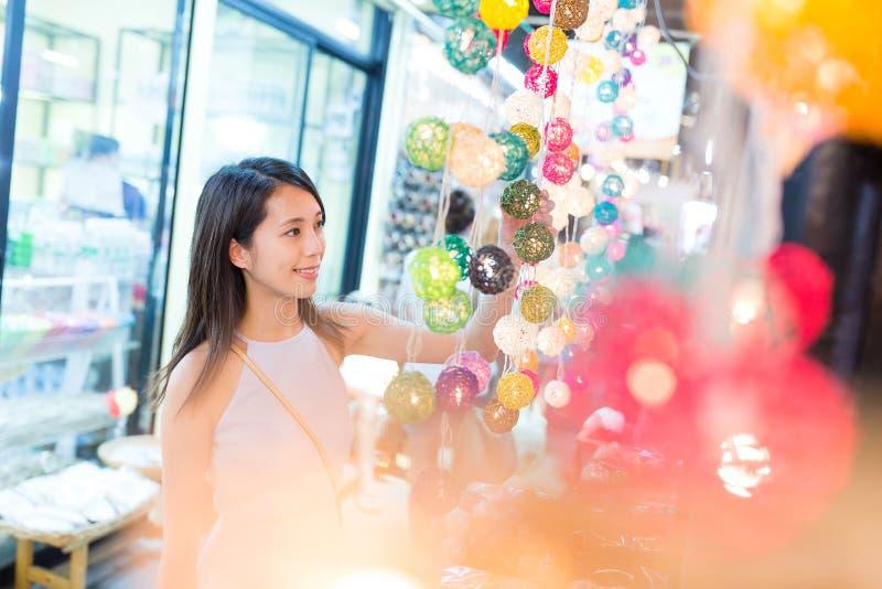 Compra da jovem mulher na loja da lâmpada fotos de stock