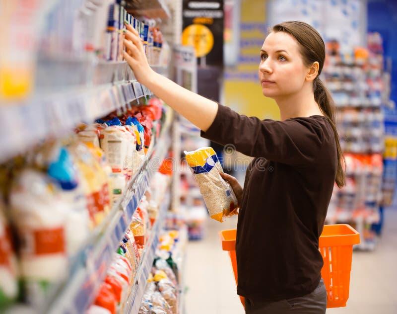 Compra da jovem mulher para o cereal, volume em um supermercado do mantimento imagem de stock royalty free