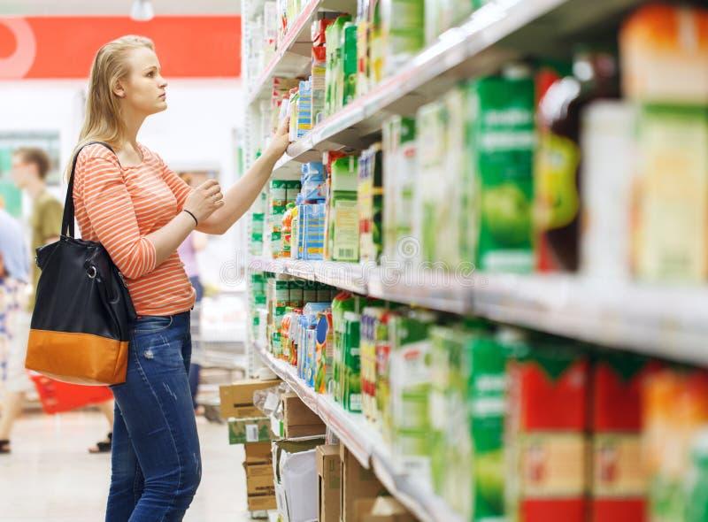 Compra da jovem mulher para o suco no supermercado fotos de stock