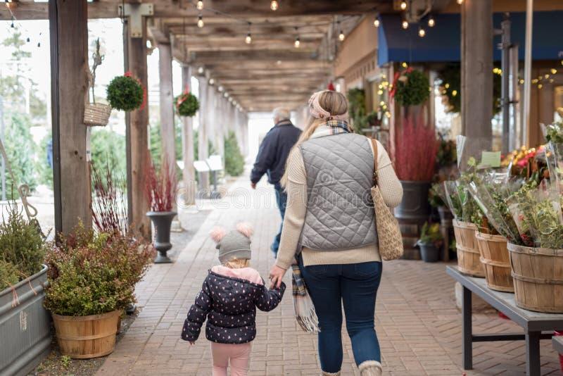Compra da jovem mulher para verdes do feriado no Garden Center exterior fotos de stock