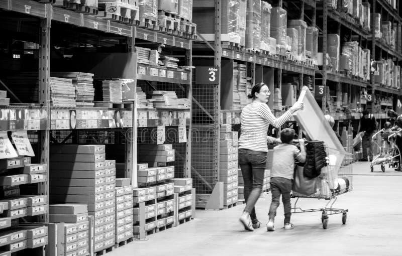 Compra da mãe solteira na loja de móveis de IKEA que empurra o carro imagem de stock