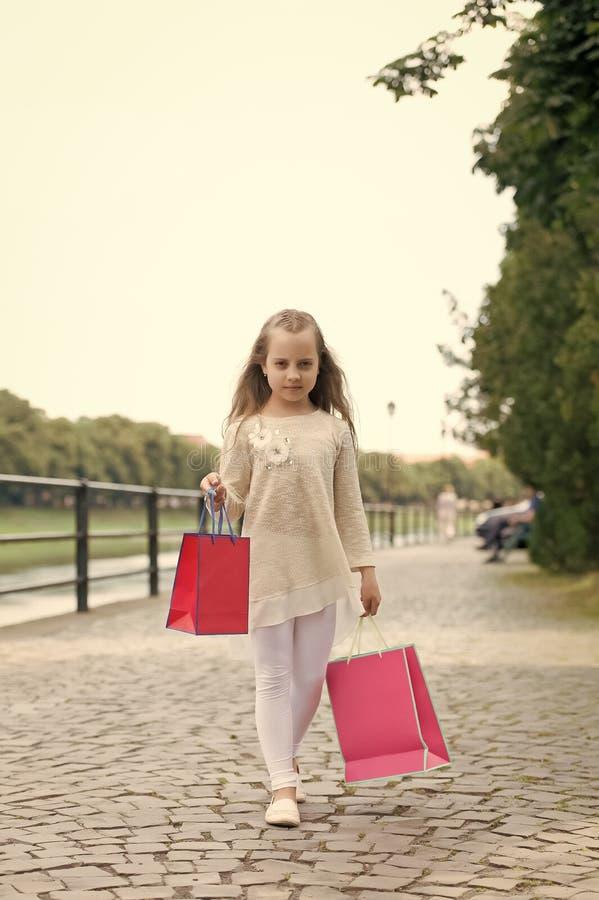 A compra da menina na cara calma leva sacos, fundo urbano Caçoe a menina com o cabelo longo afeiçoado da compra Menina do Fashion foto de stock royalty free