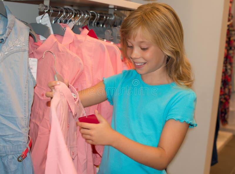 Compra da menina na loja da roupa A criança escolhe o vestido na loja de roupa imagem de stock royalty free