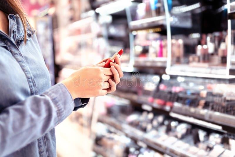 A compra da mulher compõe na seção dos cosméticos na loja Produtos de beleza de compra do cliente Escolhendo o batom vermelho da  foto de stock