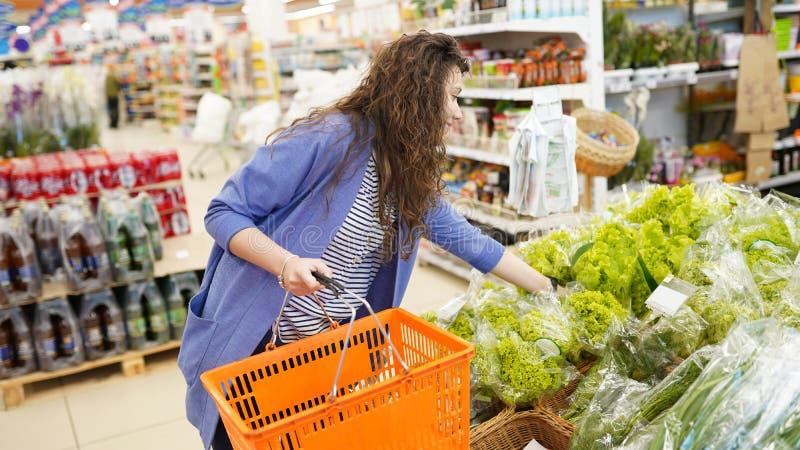 Compra da mulher no supermercado jovem mulher que pegara, escolhendo a salada frondosa verde na mercearia Estilo de vida saud?vel imagens de stock royalty free