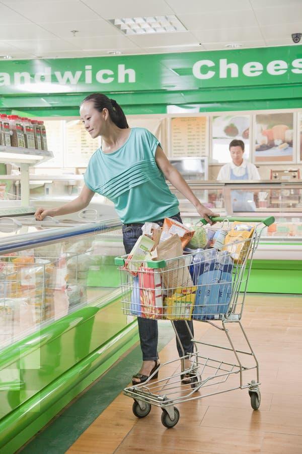 Compra da mulher no supermercado, olhando para baixo na seção refrigerada, Pequim fotografia de stock