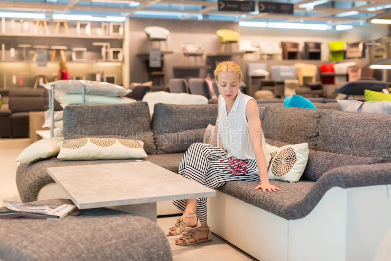 Compra da mulher para a mobília, o sofá e a decoração home na loja imagens de stock