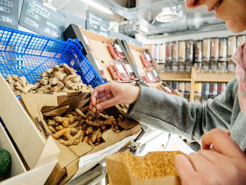 Compra da mulher para o supermercado fresco dos rizomas da curcuma da cúrcuma imagem de stock