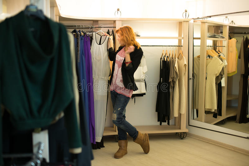 Compra da mulher que escolhe os vestidos que olham no espelho incerto fotografia de stock royalty free