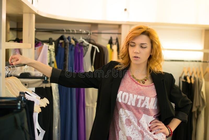 Compra da mulher que escolhe os vestidos que olham no espelho incerto imagens de stock royalty free