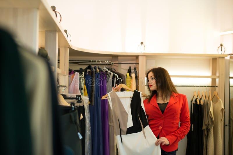 Compra da mulher que escolhe os vestidos que olham no espelho incerto fotos de stock royalty free
