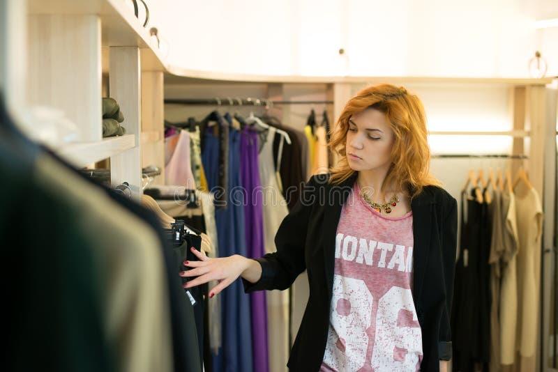 Compra da mulher que escolhe os vestidos que olham no espelho incerto imagens de stock