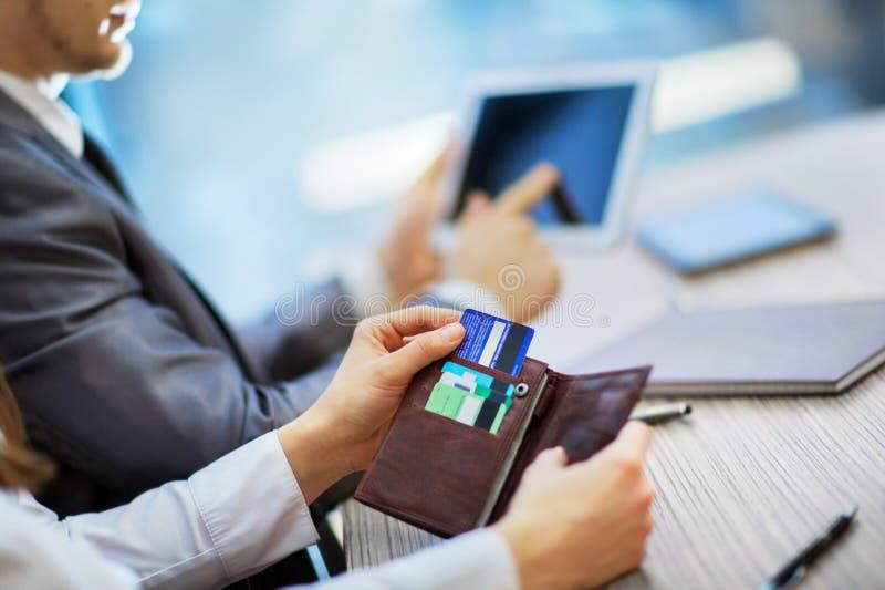 A compra da mulher que usa a bolsa retira um cartão de crédito imagens de stock royalty free